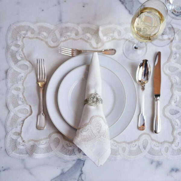 Embroidered white italian placemats in a table.