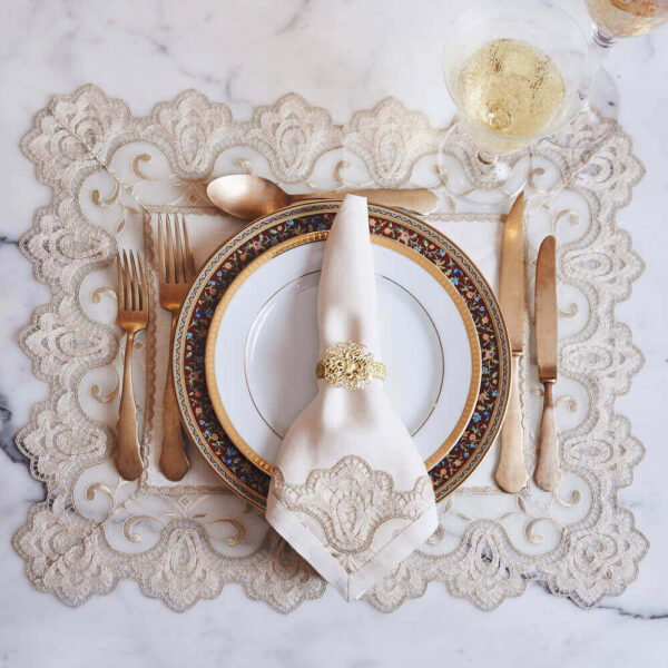 Golden embroidered placemats set in a table.