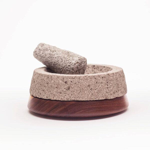 Stone and dark wood mortar and pestle with white background.