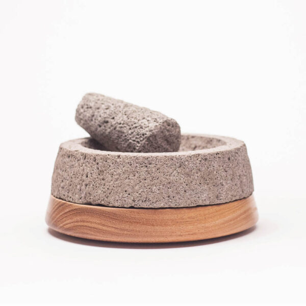 Stone and light wood mortar and pestle with white background.