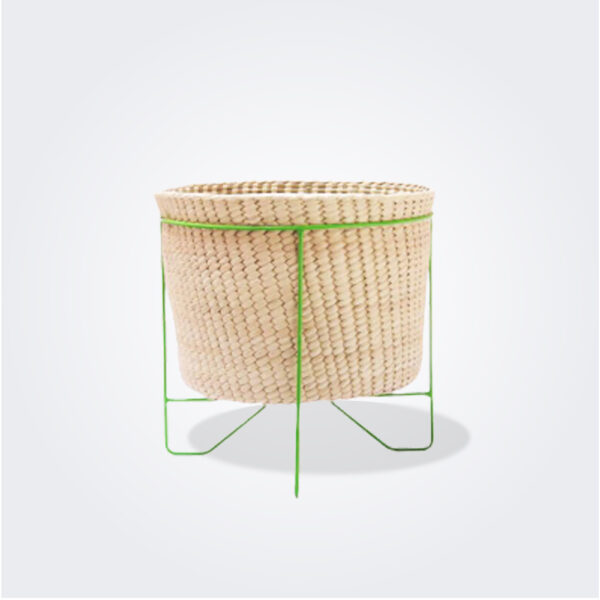 Palm leaf basket with green stand small gray background.
