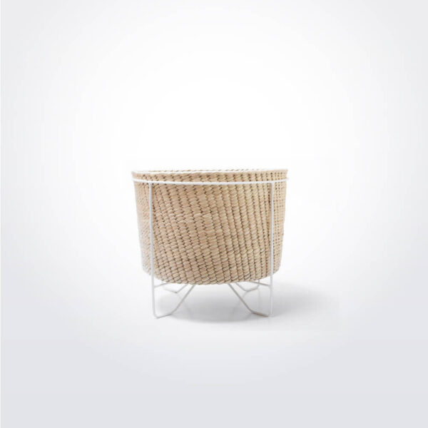 Palm leaf basket with white stand small gray background.