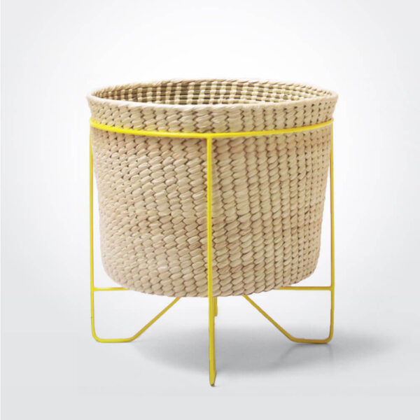 Palm leaf basket with yellow stand large gray background.