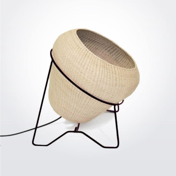 Palm leaf lamp with black stand.