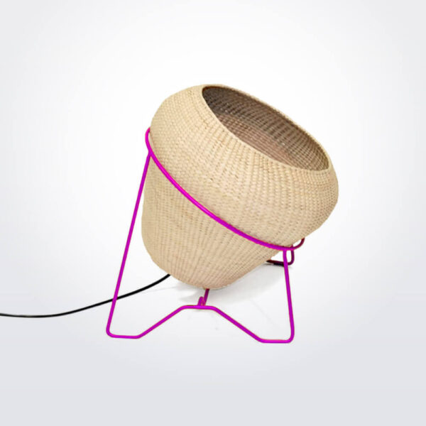 Palm leaf lamp with pink stand.