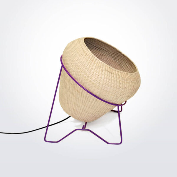 Palm leaf lamp with purple stand.