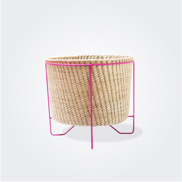 Small palm leaf basket with pink stand on gray background.