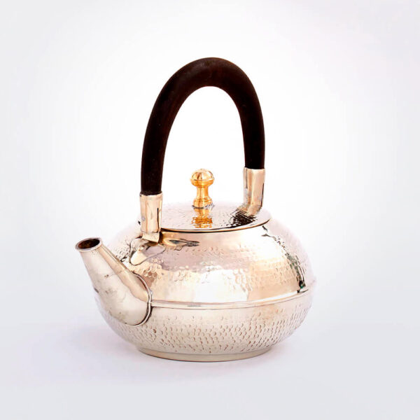 Moroccan silver hammered teapot gray background.
